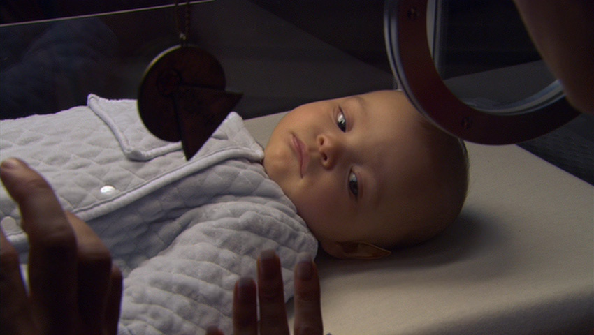 T'Pol hangs an IDIC medallion on the incubator of her ailing half-human child.